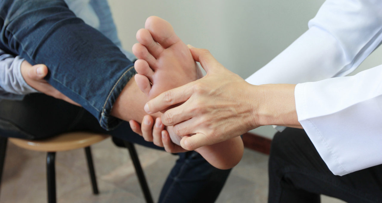 Closeup of Man feeling pain in her foot and doctor the traumatologist examines or treatment on white background, Healthy concept